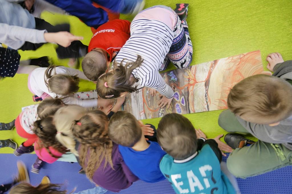 Dzieci na podłodze prezentują rysunek na bardzo szerokim arkuszu