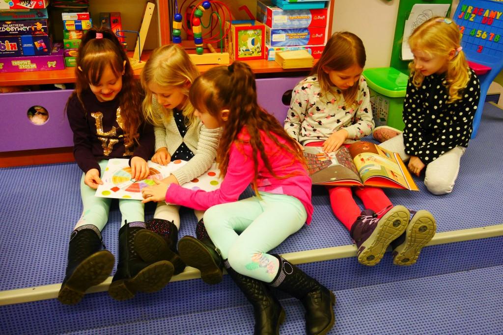Pięcioro dziewczynek siedzi i ogląda książki