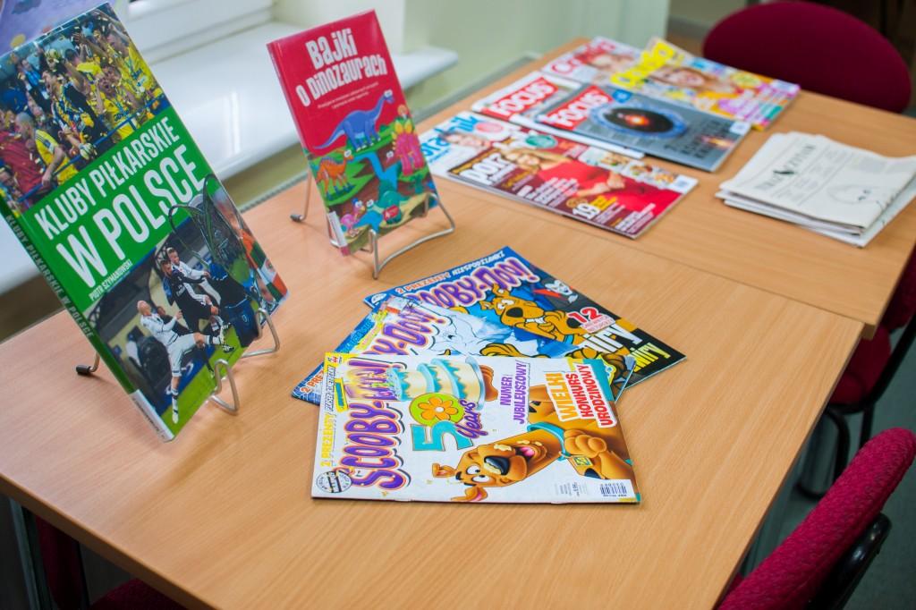 Na stole leżą czasopisma i książki na prezenterach