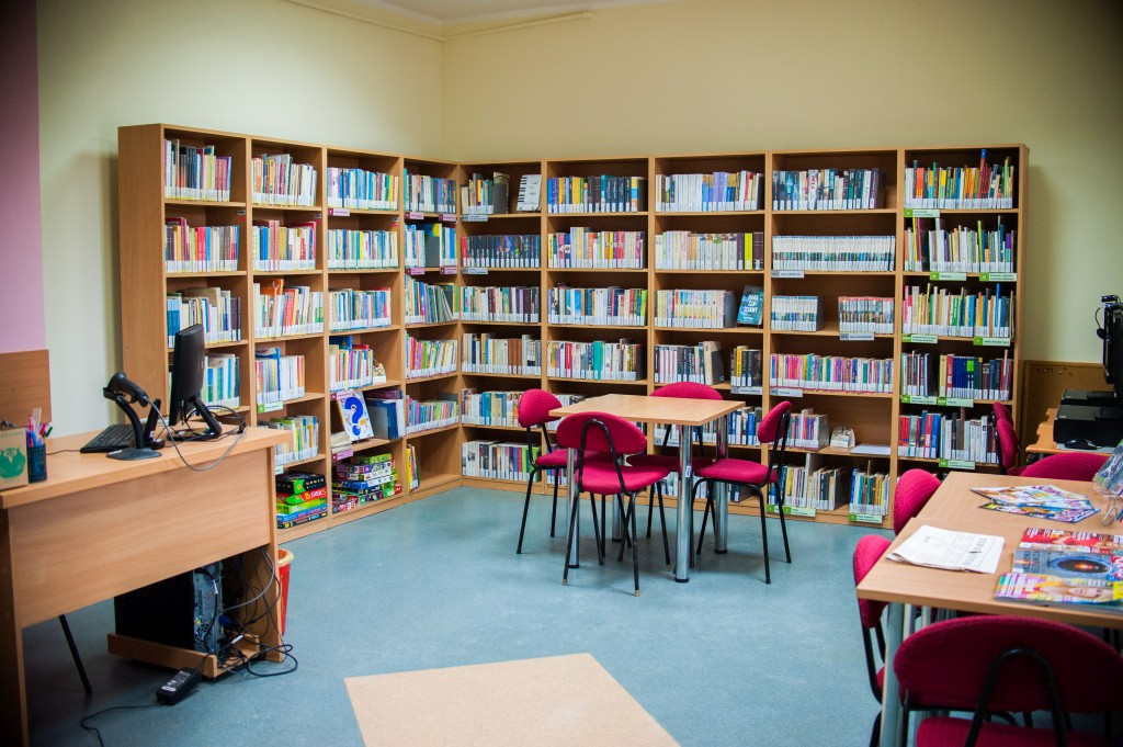 Regały, stół z 4 krzesłami i lada biblioteczna