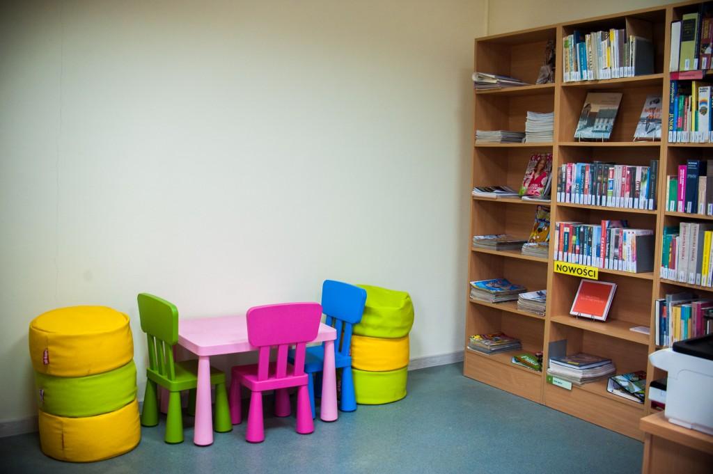 Mały stolik z 3 krzesełkami, 3 pufy, obok regał z książkami i czasopismami