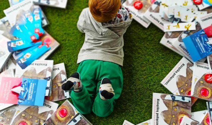 Kilkuletnie dziecko leży na brzuszku na podłodze, a wokół niego okrąg z porozrzucanych książek