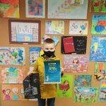 Laureat Błażej Gurgielwicz w maseczce na twarzy trzyma przed sobą dyplom, za nim ściana z wystawą prac konkursowych