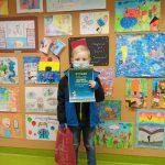 Laureat Filip Jędrych w maseczce na twarzy trzyma przed sobą dyplom, za nim ściana z wystawą prac konkursowych