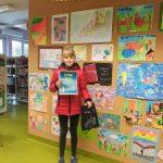 Laureatka Malwina Dąbkowska trzyma przed sobą dyplom, za nią ściana z wystawą prac konkursowych