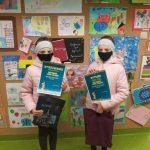 Laureatki Marta i Amelia Milczanowska w maseczkach na twarzy trzymają przed sobą dyplomy, za nimi ściana z wystawą prac konkursowych