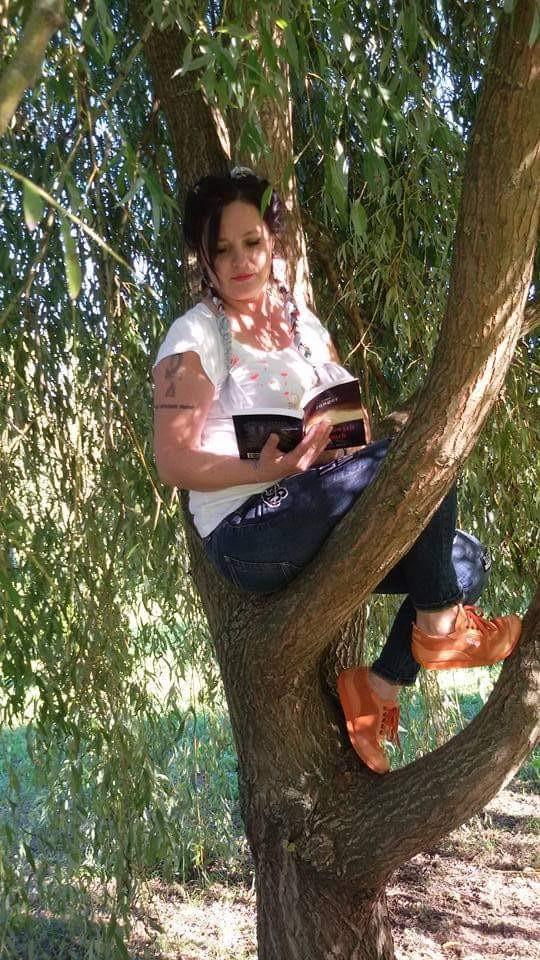 Pani siedzi na gałęzi na drzewie i czyta książkę