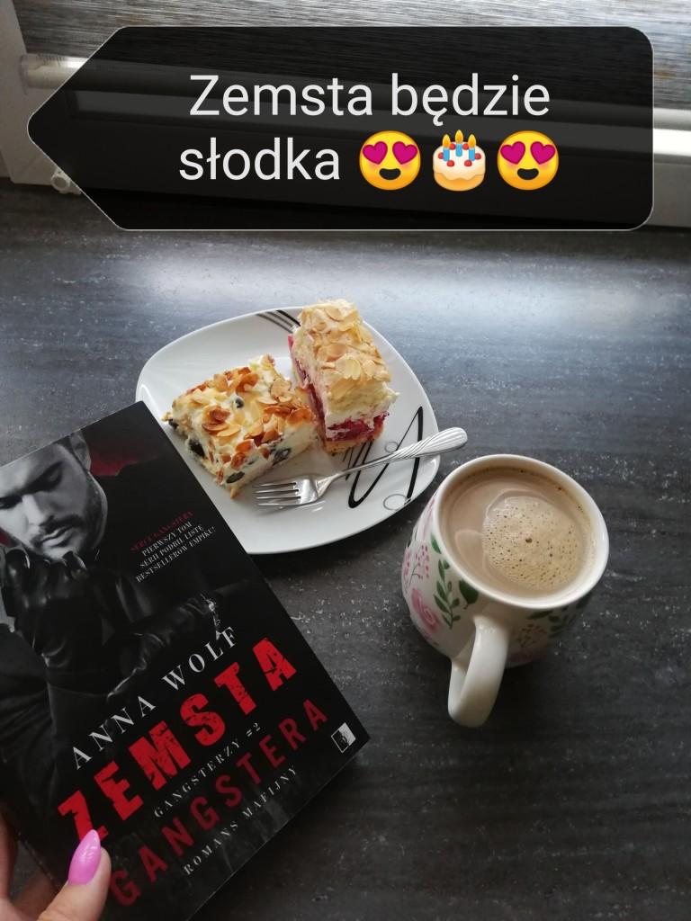 """Na stole leżą książka pt. """"Zemsta gangstera"""", talerzyk z dwoma kawałkami ciasta i kubek kawy; na górze podpis """"Zemsta będzie słodka"""" zakończony emotikonami serduszek i tortu"""