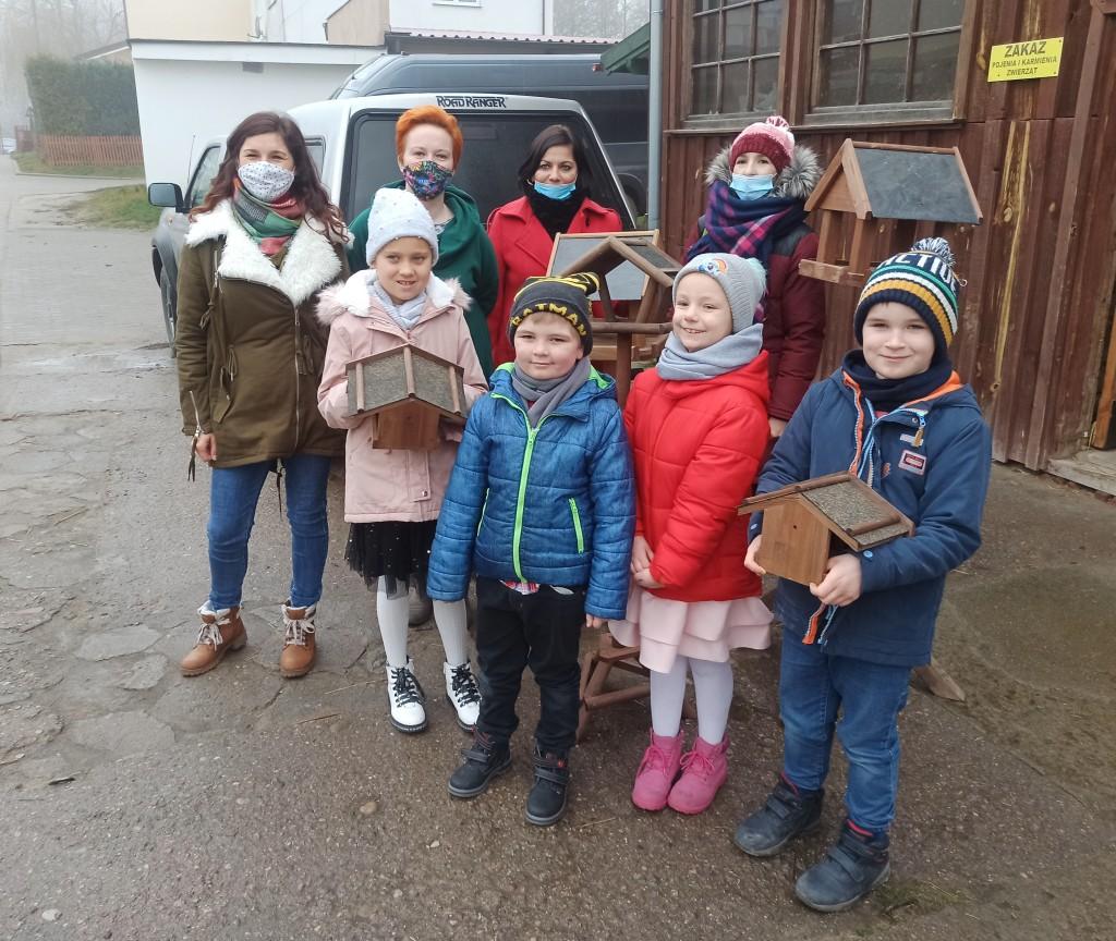 4 dzieci i 4 dorosłych pozuje do zdjęcia, 2 dzieci trzyma karmniki dla ptaków, 2 karmniki stoją między nimi, w tle ulica budynki i samochody