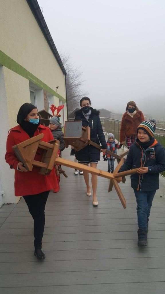 Dzieci i dorośli idą wzdłuż budynku niosąc karmniki dla ptaków