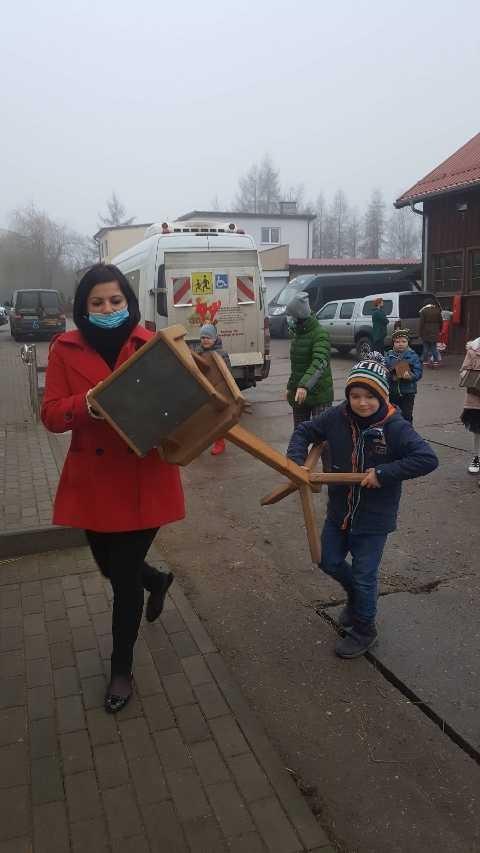 Dziecko i dorosły niosą wspólnie karmink dla ptaków, w tle ulica, chodnik i inni uczestnicy