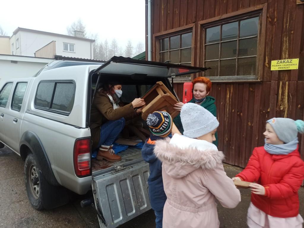 Wyładowywanie karmników z budy srebrnego pikapa, dzieci pomagają trzymać