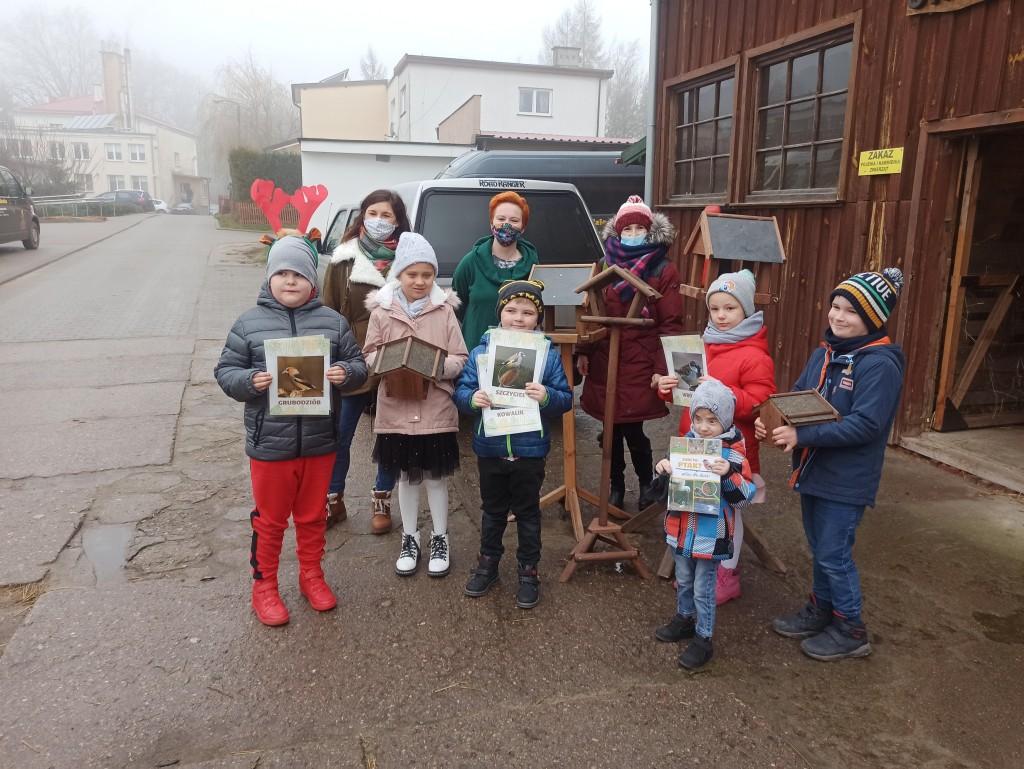 Zdjęcie grupowe 3 dorosłych i 6 dzieci, dzieci trzymają przed sobą karmniki dla ptaków lub książki o ptakach, w tle ulica, budynki i samochody