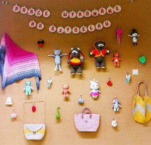"""Sciana korkowa z napisem """"Prace wykonane na szydełku"""" i z wywieszonymi eksponatami: chusta, misie i inne bajkowe stwory, torby, zawieszki, ozdoby choinkowe"""
