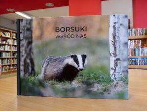 """W biblioltece na stole stoi książka """"Borsuki wśród nas"""", na okładce borsuk pośród drzew"""