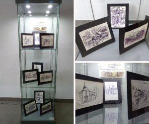 Szklana podświetlona gablota z 9 szkicami w czarnych ramkach ułożonych na trzech półkach
