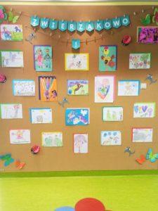 """Korkowa ściana wystawowa, na której umieszczono prace rysunkowe oraz napis """"Zwierzakowo"""""""