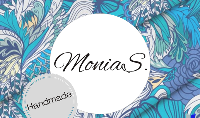 """Plakat wystawy """"Monia S. - Handmade"""", w tle wzorzysty materiał"""