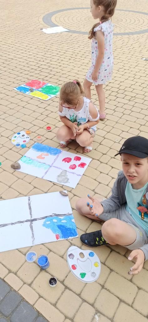 Dzieci na kostce brukowej malują prace farbami