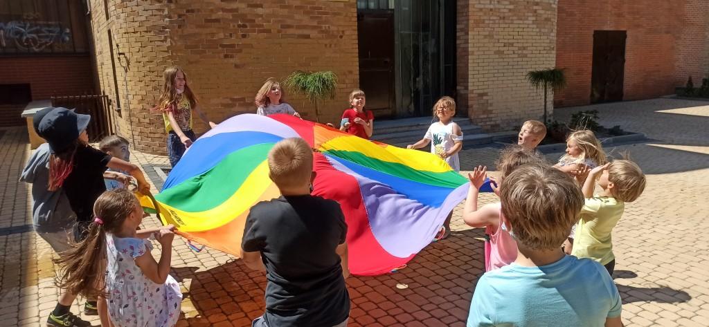 Dzieci zgromadzone wokół kolorowej płachty i poruszają nią jednocześnie