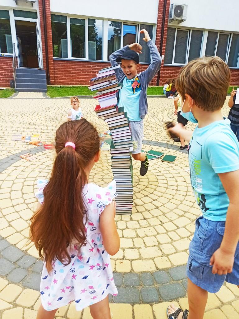 Dzieci robią wieżę z książek, ups - zaraz się zawali