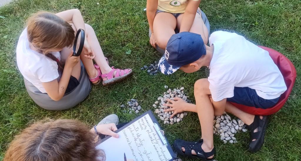 Dzieci zgromadzili na kupkach drobne kamyczki, dziewczynka używa lupy