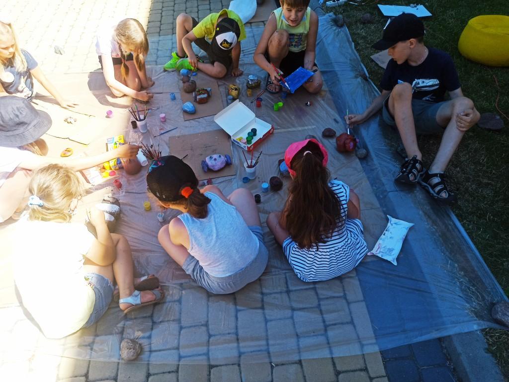 Dzieci siedzą na kostce brukowej i malują farbami kamienie