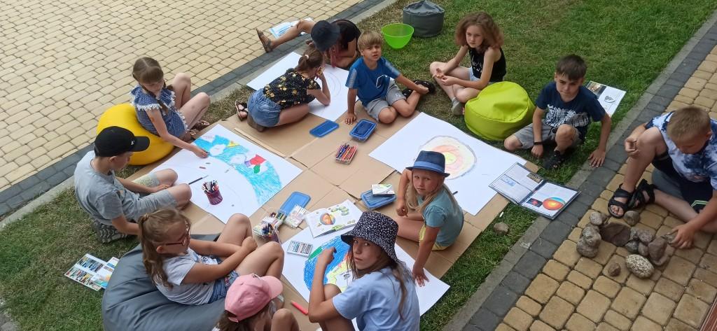 Dzieci siedzą na trawie i rysują na dużych arkuszach papieru, wśród nich leżą książki, jeden chłopiec gromadzi kamienie