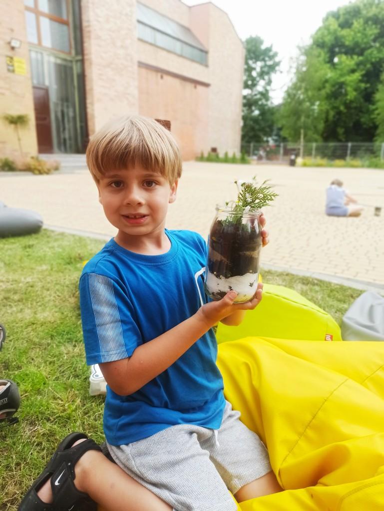 Chłopiec trzyma słoik z ziemią i roślinką na wierzchu
