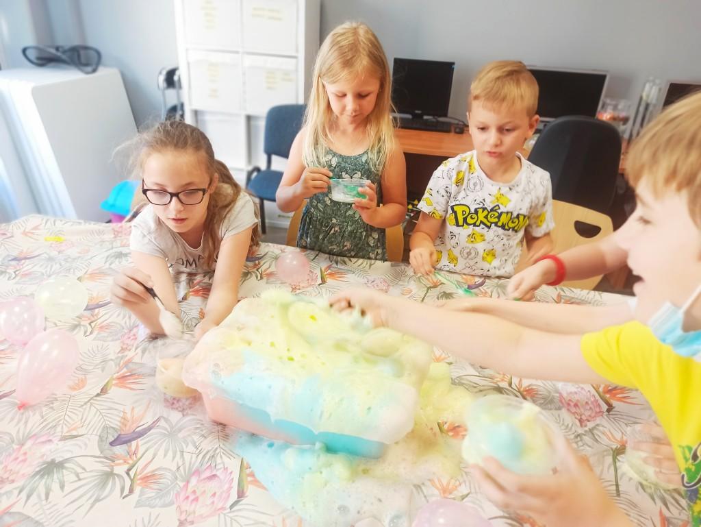 Dzieci przy stole, na którym w pojemniku buzuje kolorowa piana