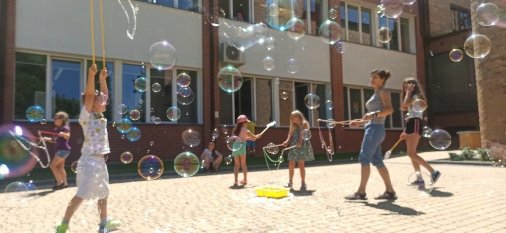 Dzieci na placu puszczają bańki mydlane