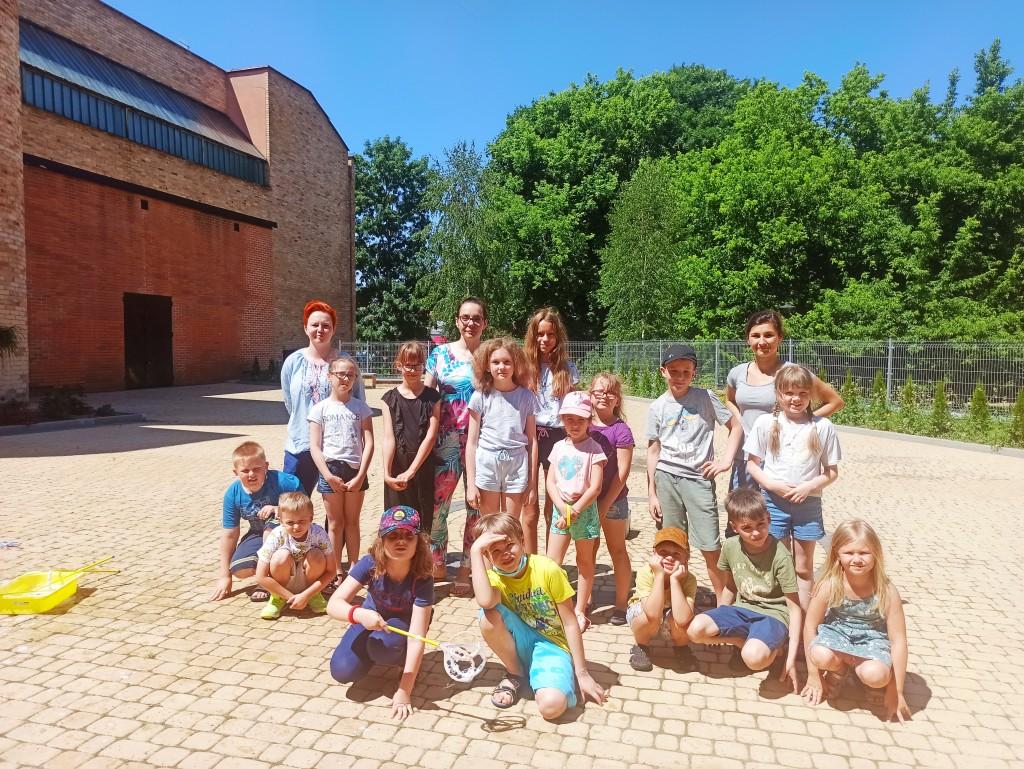 Grupowe zdjęcie dzieci i organizatorów na placu za biblioteką