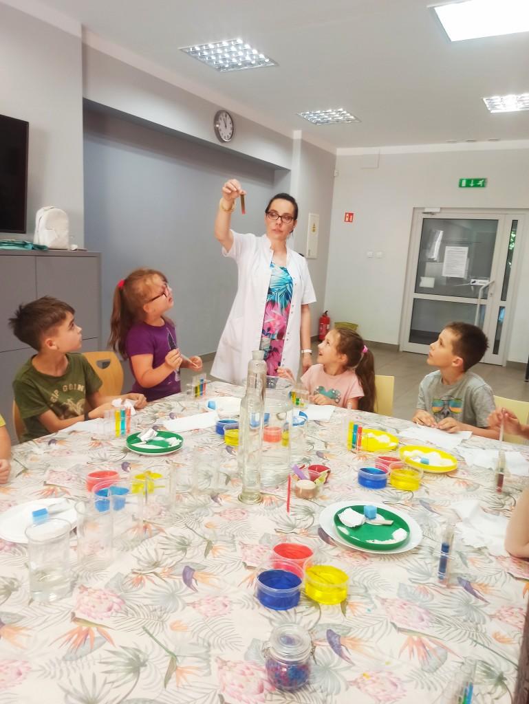 Dzieci przy stole z talerzykami i pojemnikami z kolorowymi płynami obserwują prowadzącą trzymającą fiolkę z substancją