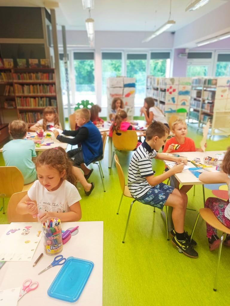 Dzieci przy stolikach wykonują prace plastyczne