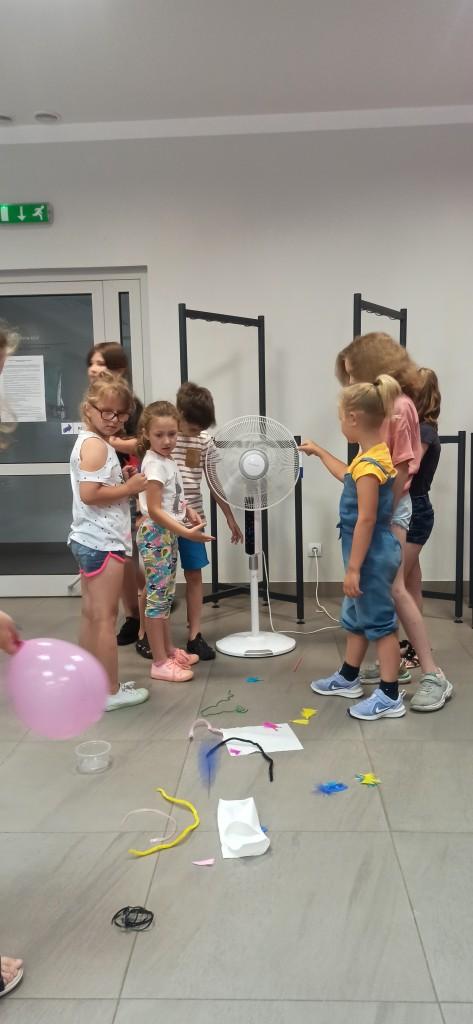 Dzieci przy uruchomionym wentylatorze upuszczają mini spadochrony