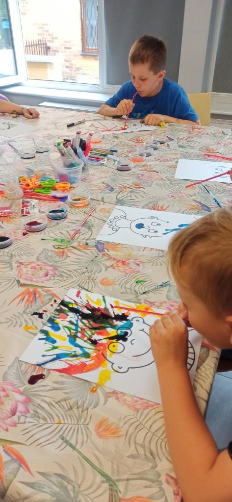 Dzieci tworzą prace plastyczne poprzez wydmuchiwanie farby słomką