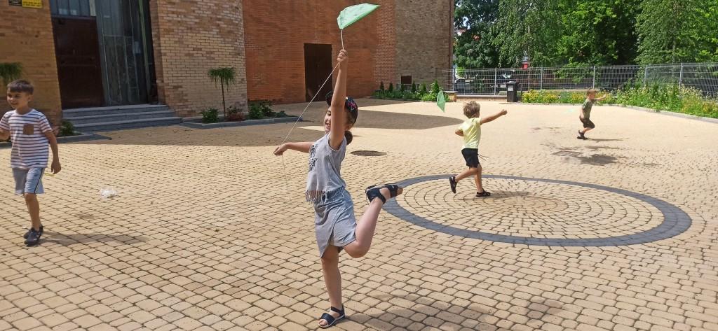Dzieci biegają po placu z latawcami