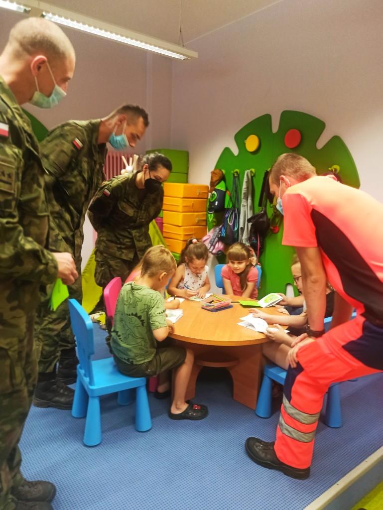 Dzieci rysują przy stole, dookoła nich żołnierze przypatrują się