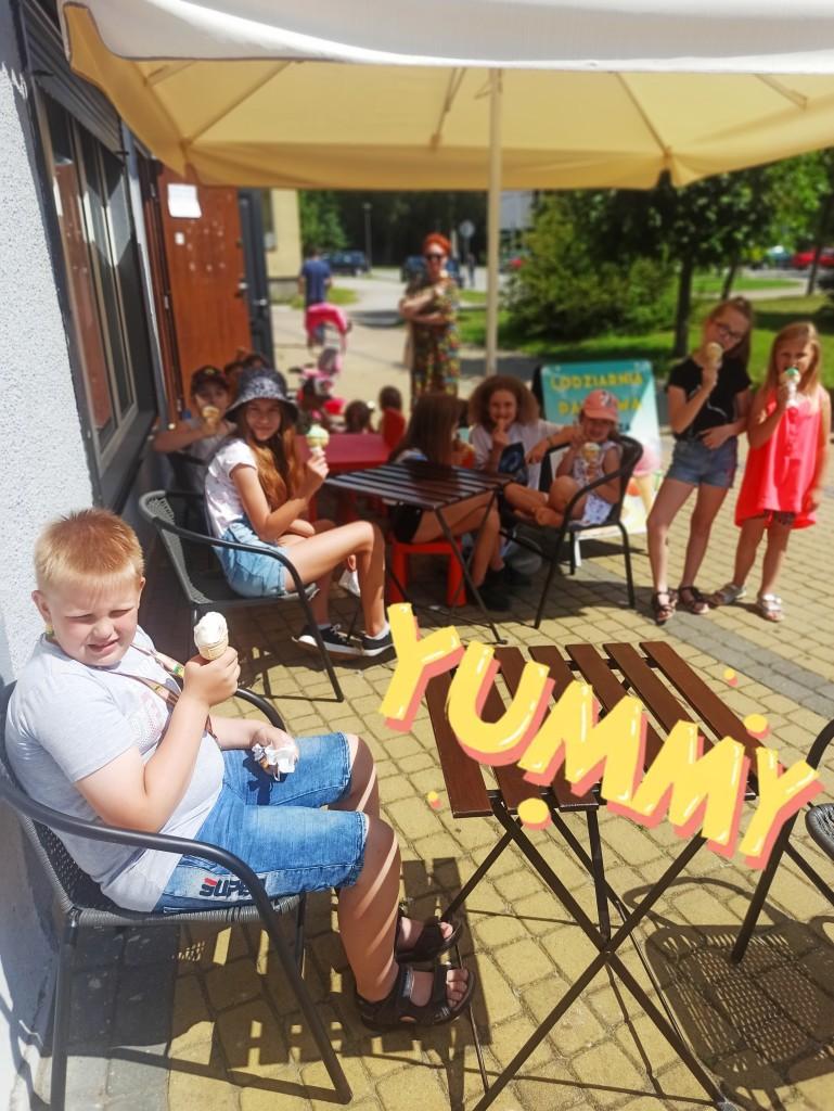 Dzieci siedzą przy stołach obok lodziarni i spożywają lody