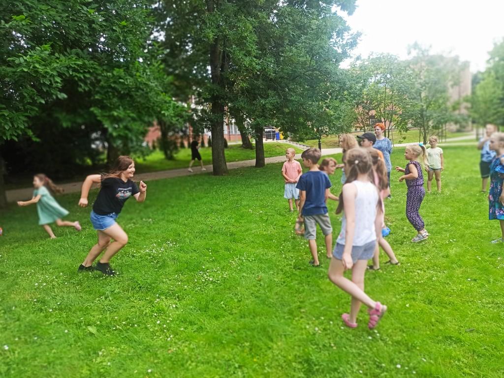 Dzieci biegają na trawniku w parku