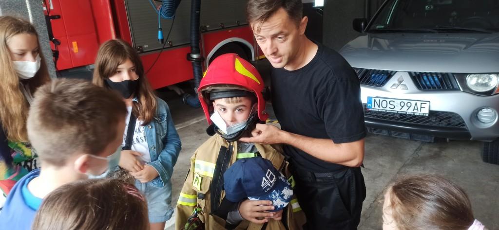 Funkcjonariusz przebierając dziecko opisuje strój strażaka