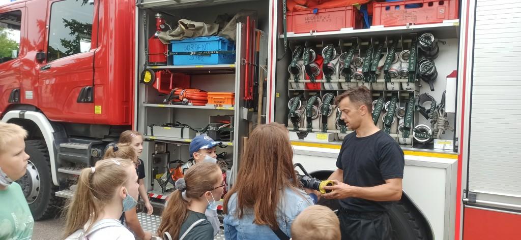 Strażak przedstawia dzieciom wyposażenie wozu gaśniczego