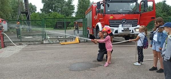 Dziewczynka w kasku przy asyście strażaka leje wodę z sikawki