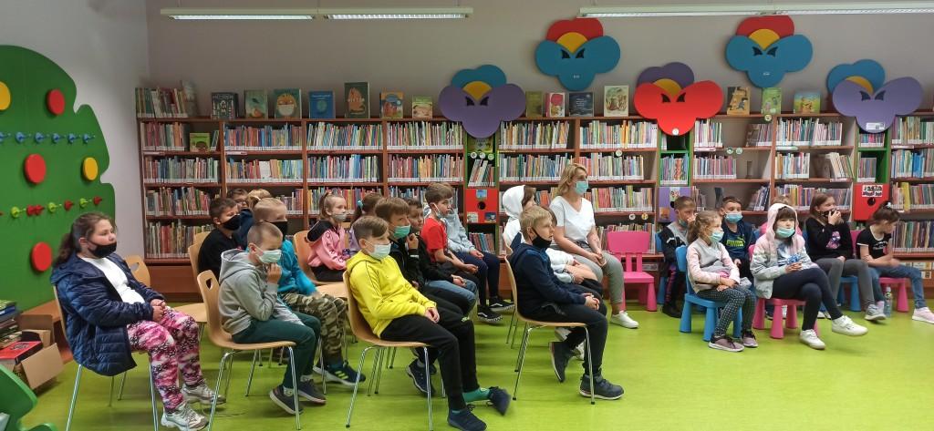 Przybyli uczniowie siedzą na krzesełkach i wysłuchują wypowiedzi autorki