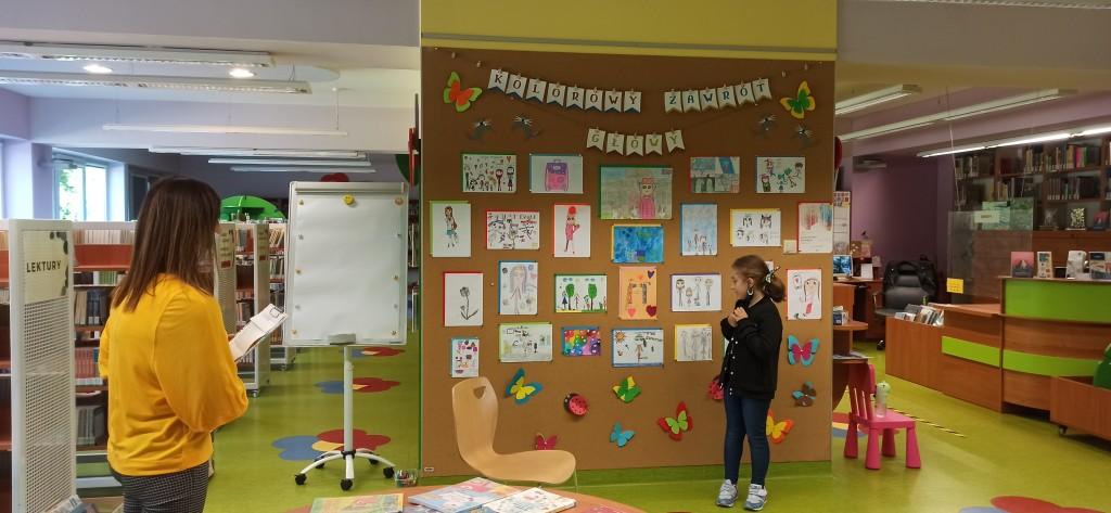 Autorka stoi przed ścianą, gdzie są zaprezentowane jej prace, na skraju zdjęcia stoi tyłem bibliotekarka